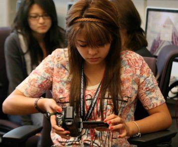 Yetzabell Rojas studies her handheld camcorder during videography class in Phoenix, Friday June 3, 2011. (SJI Photo/Rachel Jimenez)
